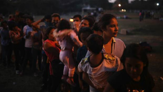 Central American migrant women and children stand in line for food during the annual Migrant Stations of the Cross caravan