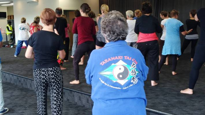 Womad campers getting into tai chi during a free class at the 2018 festival .