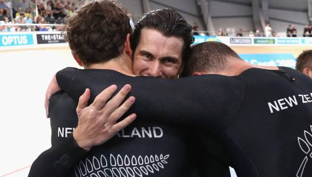Sam Webster facing is embraced by NZ team sprint team-mates Ethan Mitchell left and Eddie Dawkins after winning gold