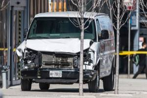 Toronto police officers stand near a damaged van after it was driven into pedestrians, killing at least 10.