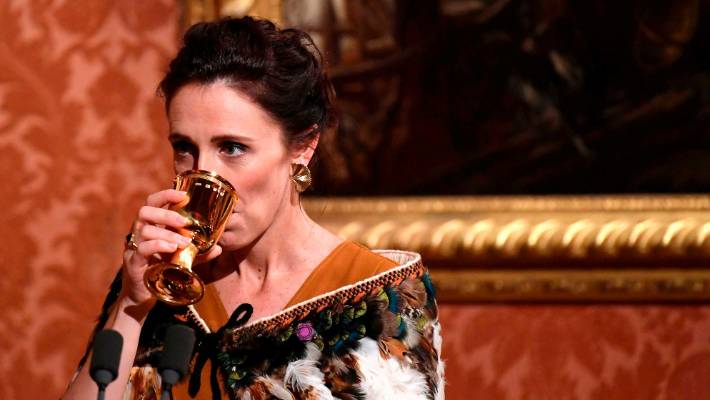 New Zealand's Prime Minister Jacinda Ardern sips on a drink as she delivers a speech at a dinner hosted by Queen Elizabeth II wearing the Meadowlark's gold leaf like design Vita Earrings in large, which can be bought for $3079.