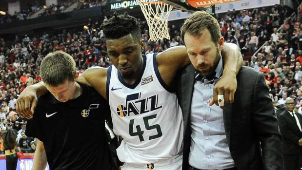 Utah Jazz guard Donovan Mitchell is helped off the court after sustaining an injury against the Houston Rockets