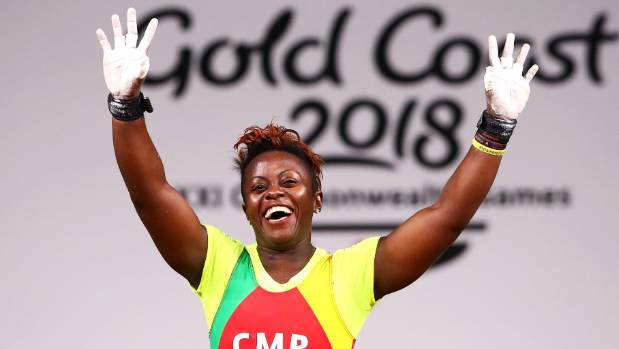 Cameroon's Arcangeline Fouodji Sonkbou waves to the crowd during the women's 69kg weightlifting final