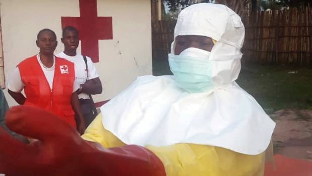 Members of a Red Cross team don protective clothing before heading out to look for suspected victims of Ebola