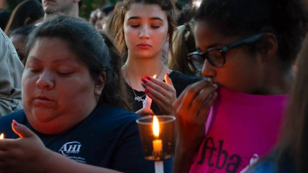 Santa Fe High School student Hunter Kana centre holds a lighted candle during a vigil held in the wake of a deadly
