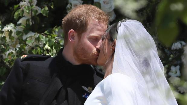 Meghan Markle and Prince Harry kiss on the steps of St George's Chapel.