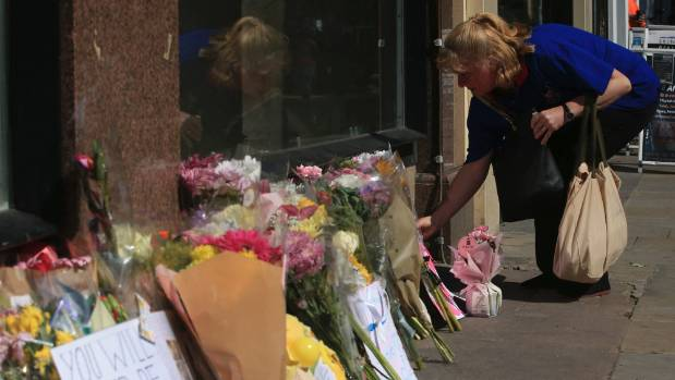 A woman leaves some flowers ahead of the Manchester Arena National Service of Commemoration at Manchester Cathedral