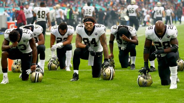 New Orleans Saints players and team kneel prior to the NFL match against the Miami Dolphins last year