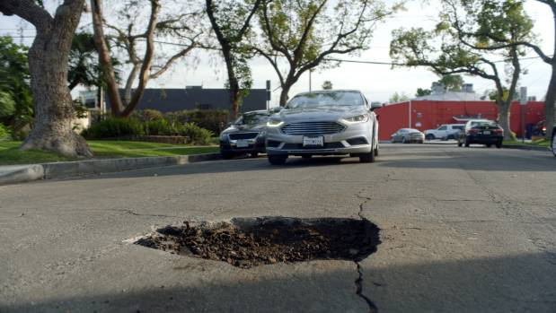 Potholes are causing massive pizza disruption problems in the USA so Domino's has decided to do something about