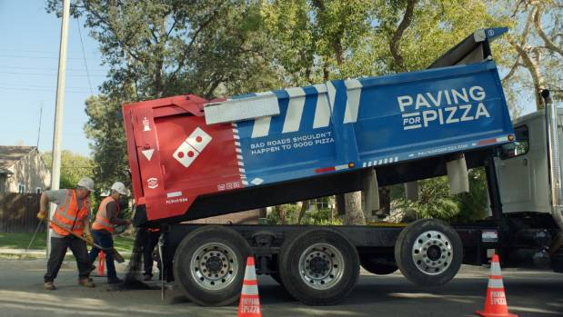 The company has launched a'Paving for Pizza campaign where it pays for pothole repairs in US towns and cities