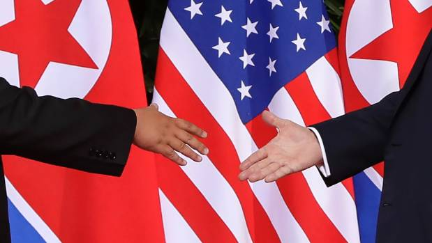 Trump, right, reaches to shakes hands with Kim during their first-ever meeting.
