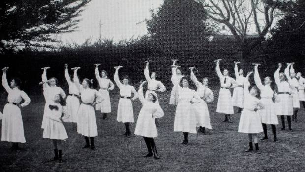 Girls excercising on the school's grass tennis.