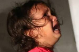 A two-year-old Honduran asylum seeker cries as her mother is searched and detained.
