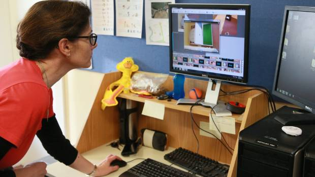 Thesis student Margaret Crawford uses cameras to monitor the dogs sniffing samples in a separate room.
