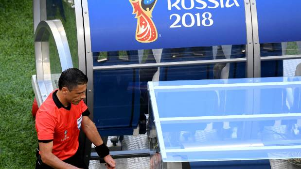 Referee Milorad Mazic consults VAR over a penalty award in a World Cup pool game.
