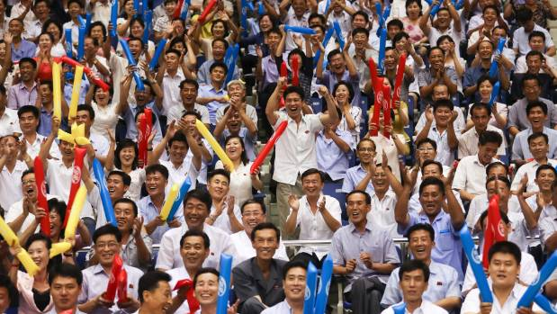 North Koreans cheer as they watch a friendly basketball game between South and North players.
