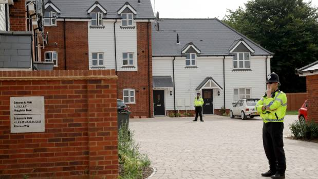 Police stand guard outside homes in Amesbury, England, after two people in the town were poisoned.