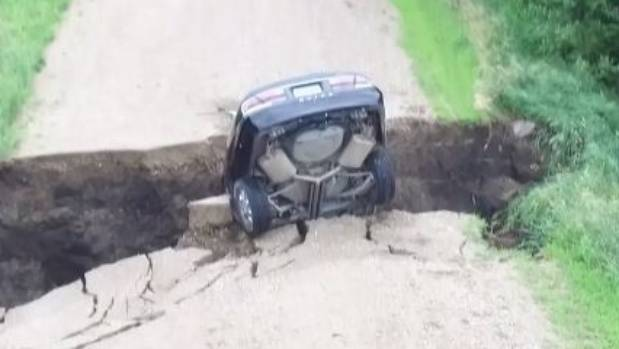 Minnesota teen escapes uninjured after driving into large hole in washed-out road
