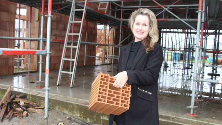 Stellaria NZ director Robyn MacPherson holds up an example of a solid clay building block, designed to move moisture and air across a house.