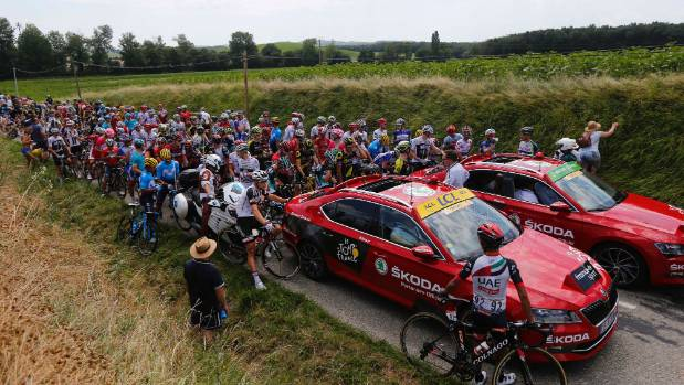 Riders wait on the road after a farmer's protest interrupted the 16th stage of the Tour de France