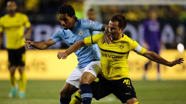 Manchester City midfielder Douglas Luis left battles over the ball with Borussia Dortmund midfielder Mario Gotze