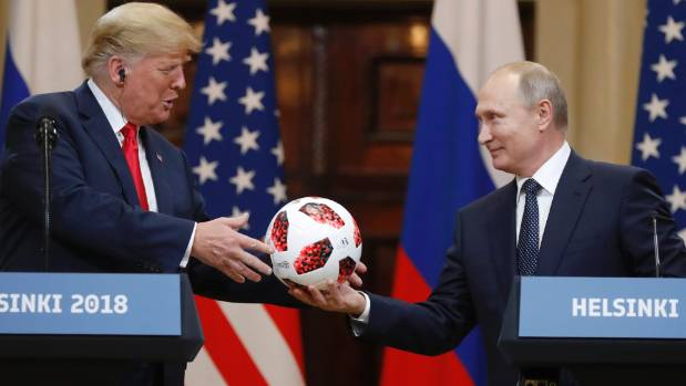 Russian President Vladimir Putin gives a soccer ball to US President Donald Trump during a press conference after their