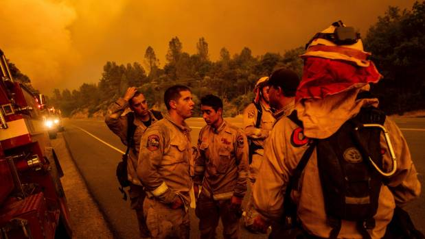 Firefighters discuss plans while battling the Carr Fire in Shasta California