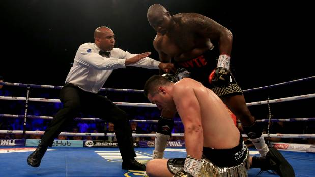 The referee gets in between the two fighters after Dillian Whyte knocks Joseph Parker to the floor during their ...
