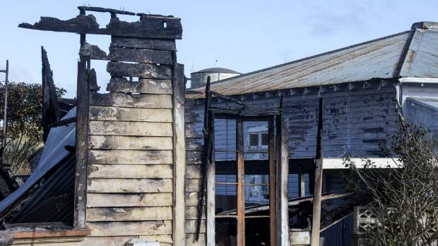 Blistered paint on a neighbouring house shows how close the fire got to spreading.