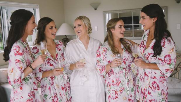 The bride and her bridesmaids share a laugh before the wedding.
