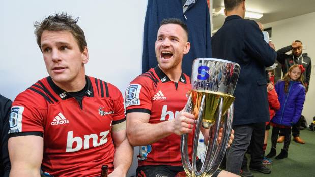 Crusaders duo Matt Todd, left, and Ryan Crotty pose with the Super Rugby trophy after their 37-18 win over the Lions.