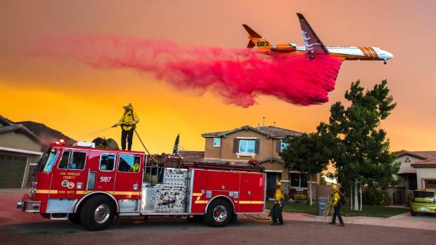 A plane drops fire retardant behind homes along Mc Vicker Canyon Park Road in Lake Elsinore California as the Holy Fire