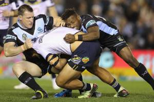 SYDNEY, AUSTRALIA - AUGUST 18: John Asiata of the Cowboys is tackled by Paul Gallen and James Segeyaro of the Sharks  ...