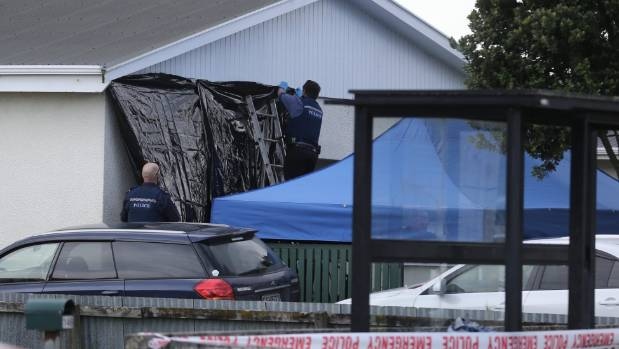 The police put a tarpaulin in front of a window at the Whanganui house where a man was shot dead.