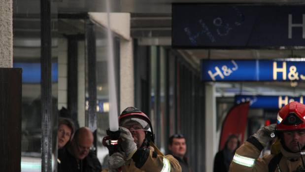 A firefighter extinguishes a smoldering fire on a shop floor in Gore & # 39; s Main Street on Wednesday.