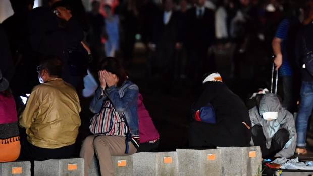 A woman covers her face as she takes shelter on a road following the 6.6 magnitude earthquake. (Yu Nakajima/Kyodo News ...