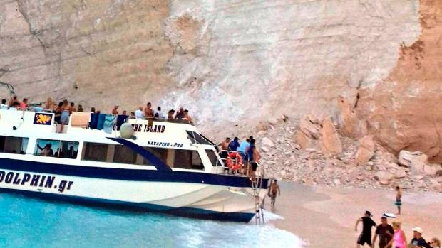 People embark a vessel after the landslide at Navagio (Shipwreck) Beach.