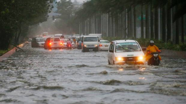 Motorists negotiate a flooded street following heavy rains and strong winds brought about by the typhoon.