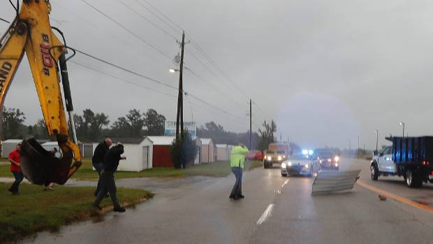 A piece of corrugated metal blown by winds from Hurricane Florence just misses a state patrolman as people move a wood and metal structure that was blown onto the roadway.