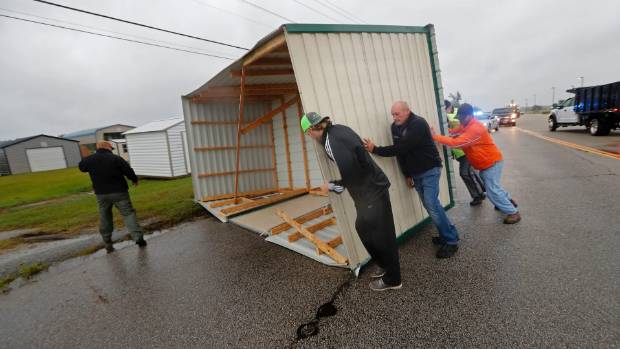 People move a wood and metal structure off a roadway after winds from Hurricane Florence blew it off a sales lot.