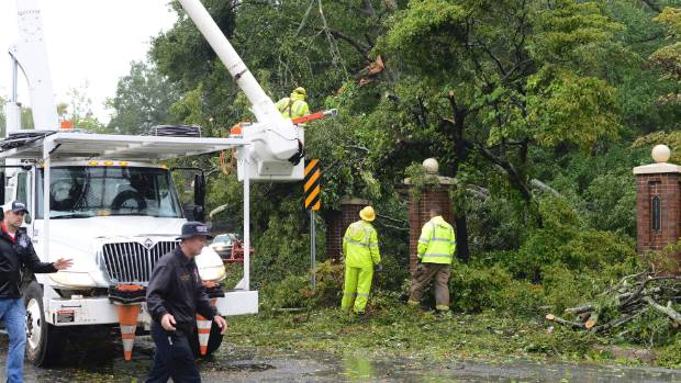 Rains from Hurricane Florence fall as crews remove tree limbs from a power line.