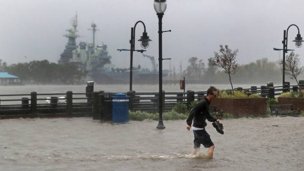 A man crosses a flooded street in downtown Wilmington, N.C., after Hurricane Florence made landfall.