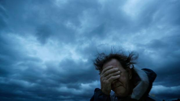 Russ Lewis covers his eyes from a gust of wind and a blast of sand as Hurricane Florence approaches Myrtle Beach, South Carolina.