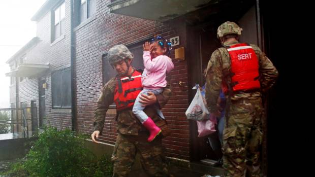A rescue team from the North Carolina National Guard 1/120th battalion evacuates a family as the rising floodwaters from Hurricane Florence threatens their home in New Bern, N.C.