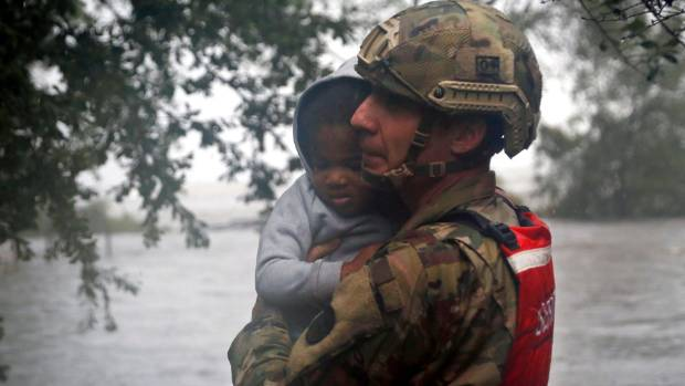 Rescue team member Sgt. Nick Muhar, from the North Carolina National Guard 1/120th battalion, evacuates a young child as the rising floodwaters from Hurricane Florence threatens his home.