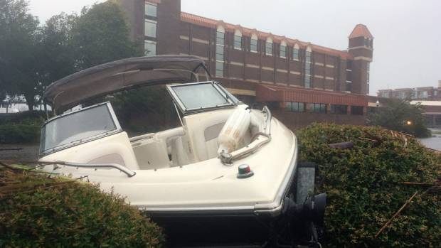A speed boat sits wedged in bushes in the parking lot of a waterfront hotel.