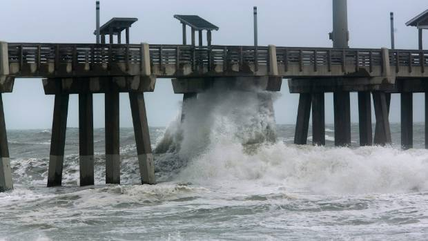 Large waves crash under Jennette's Pier in Nags Head N.C. at high tide as Hurricane Florence makes landfall further south.