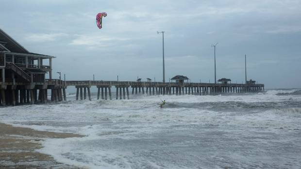 Kite Boarder Dimitri Maramenides heads out next to Jennette's Pier in Nags Head, N.C., as Hurricane Florence makes landfall.