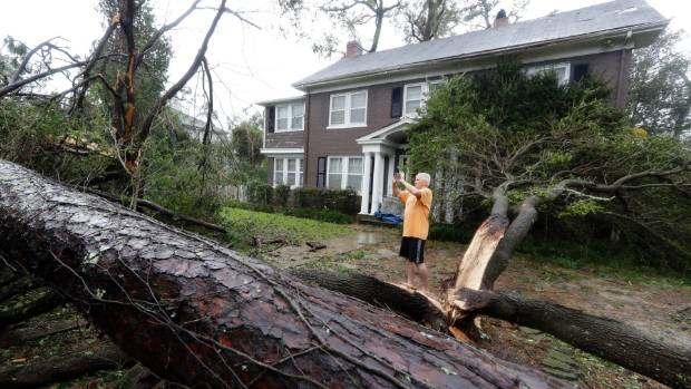 Mike Kiernan takes photos of the damage to his home in Wilmington, N.C