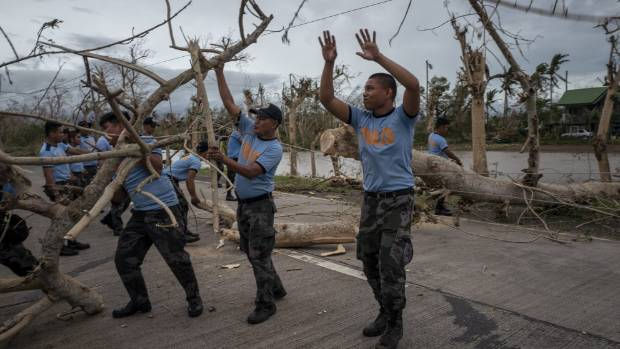 Police help clear debris on a road in northern Philippines.